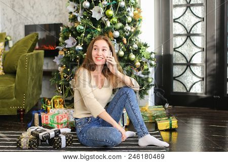 Painter Girl Talking On Smartphone, Girl Wishing Happy New Year To Friends. Young Smiling Woman Sitt
