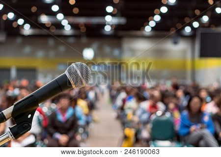 Microphone Over The Abstract Blurred Photo Of Conference Hall Or Seminar Room In Exhibition Center B