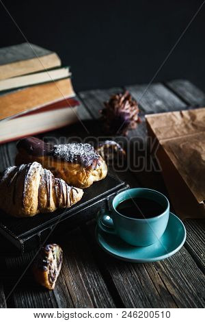 Croissant And White Cup Of Black Coffee On Brown Canvas. A