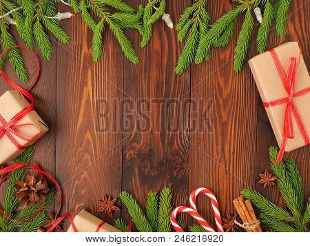 Christmas And Happy New Year Dark Brown Background. Gift Christmas Box, Fir Branches, A Wooden Table