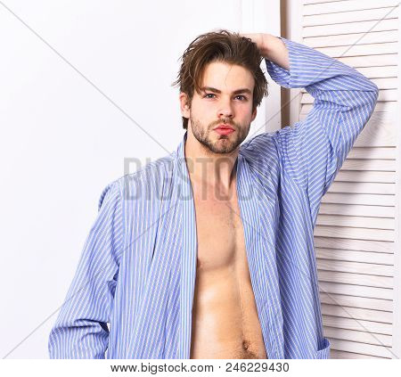 Fit guy with sexy body in home or bath clothes. Morning, spa and masculinity concept. Man with beard in blue dressing gown on white background. Macho in bathrobe with torso and six packs. poster