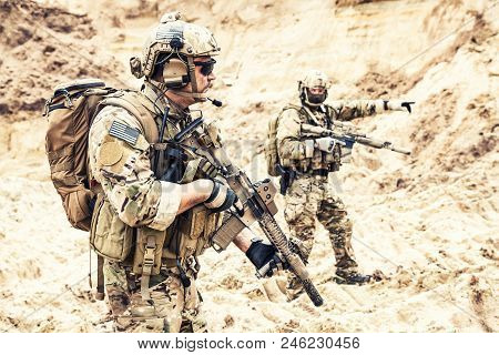 Two armed US army commandos or military scouts equipped with radio headset moving forward in sands during enemy area reconnaissance. Special forces operation, long range surveillance mission in desert poster