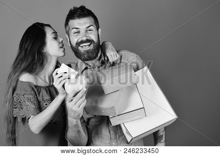 Shopping And Free Time Concept. Man With Beard Holds Credit Card And Piggy Bank. Guy With Beard And