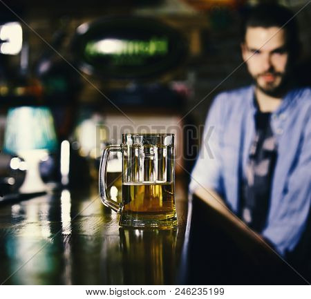 Service Concept. Guy Sits At Bar Counter With Beer. Glass Of Draft Beer On Blurred Bar Background. M