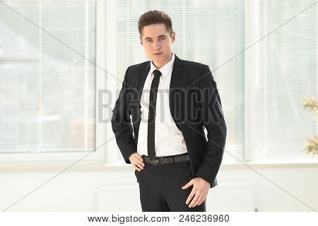 Full Growth.confident Young Businessman Standing In Office.photo With Place For Text