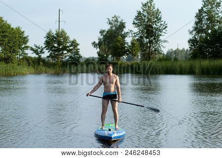 A Man Stands On A Sap Board With An Oar And Swims Through A Forest Lake, Active Rest On The Water