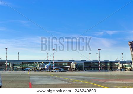 Passenger Airplane At Stationary Terminal Gates On Airport Runway, Marupe, Riga, Latvia. Road Transp