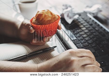 Unhealthy Snack At Work Time. Woman Eating Muffin At Workplace. High Calorie, Fattening Junk Food, W