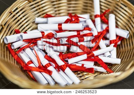 Pile Of Small Paper Scrolls In Wicked Basket.  White Scrolls Tied With Red Ribbon. Future Prediction