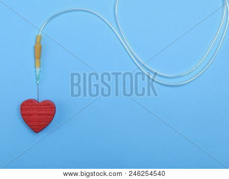 Plastic Catheter With Needle And Red Heart On Blue Background