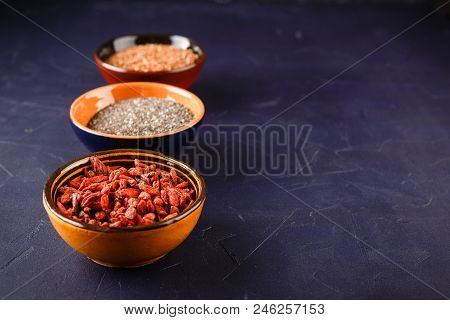 Super Foods - Chia Seeds, Flax Seeds And Goji Berries In Three Ceramic Bowls