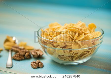 Tasty Cornflakes With Walnut In Glass Bowl On Blue Background. Corn Flakes