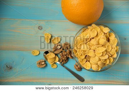 Tasty Cornflakes With Walnut In Glass Bowl On Blue Background. Top View. Corn Flakes. Healthy Breakf