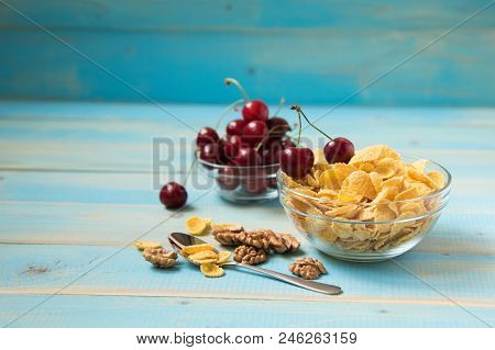 Tasty Cornflakes With Walnut And Cherry In Glass Bowl On Blue Background. Corn Flakes. Ealthy Breakf