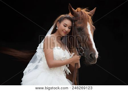 Young Beautiful Beauty Bride In Fashion White Wedding Costume Stand With Handsome Horse On Black Bac