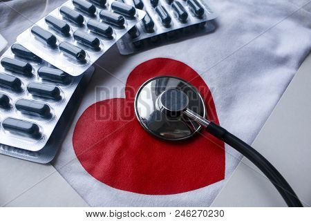 Stethoscope And A Few Blisters Of Pills With Red Heart On White Background. Day Of Cardiologist, Hea
