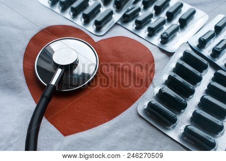 Red Heart, Stethoscope And Bunch Of Blisters With Green Pills On The White Canvas Background. A Conc