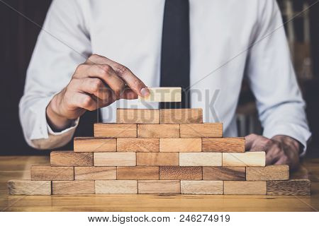 Risk To Make Business Growth Concept With Wooden Blocks, Hand Of Man Has Piling Up And Stacking A Wo