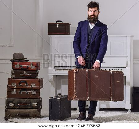 Macho Elegant On Strict Face Stands Near Pile Of Vintage Suitcase, Holds Suitcase. Man, Traveller Wi