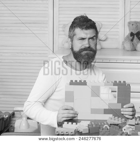 Parenthood Concept. Man With Beard And Mustache Holds Construction Made Out Of Plastic Bricks. Guy W