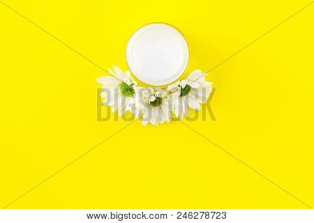 Natural Emollient Chamomile Cream. White Cream In Small Jar Near Chamomile Flowers On Yellow Backgro