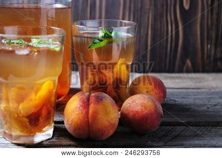 Fresh Homemade Peach Sweet Tea With Mint On Wooden Table.