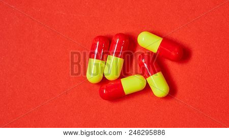 Pills Spilling Out Of Pill Bottle On Red. Top View With Copy Space. Medicine Concept