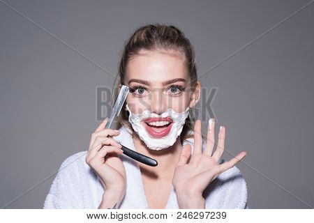 Girl on smiling face wears bathrobe, grey background. Lady play with sharp blade of straight razor. Woman with face covered with foam holds straight razor in hand. Barber and shaving concept. poster