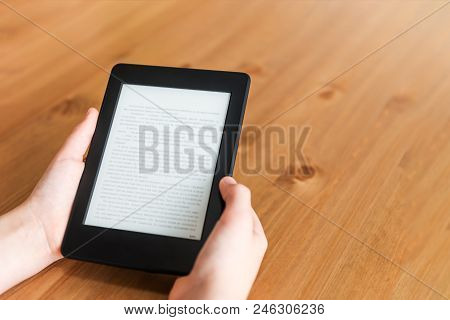 Girl Is Reading Ebook On Digital Tablet Device While Sitting At The Table