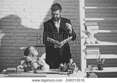 Home Education Concept. Kid And Man By Desk With School Supplies. Schoolgirl And Tutor With Happy Fa