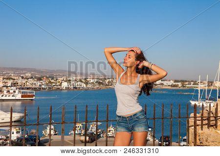 Beautiful Tourist Woman On The Old Castle On Mediterranean Sea Coast. Paphos, Cyprus. Bright Sunset