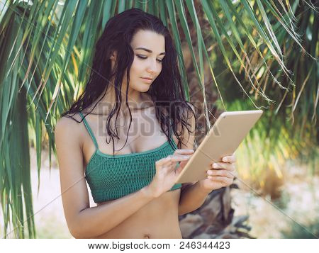 Traveler Woman Using Tablet Computer In Tropical Jungle Symbolizing The Ability To Blend Work And Re