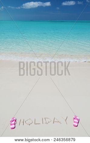 HOLIDAY writing on the sandy beach of Exuma, Bahamas