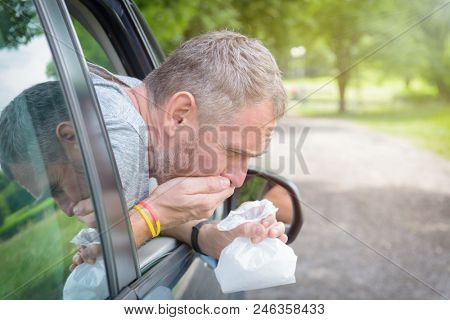 Man suffering from motion sickness in a car and holding sick bag