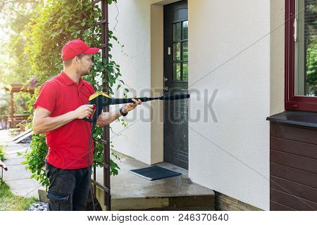Worker With High Pressure Washer Cleaning House Facade