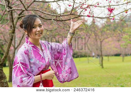 Asian Woman Standing Under The Cherry Tree And Raise Up Her Hands To Introduce The Sakura And Take A