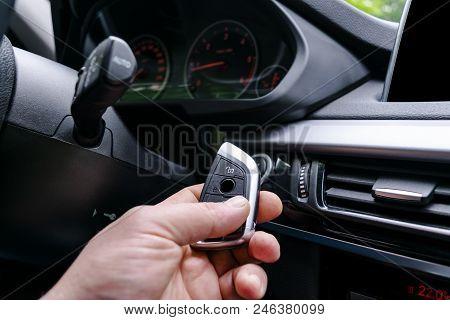 Closeup Inside Vehicle Of Man Hand Holding Wireless Key Ignition. Start Engine Key. Hand Holding Car