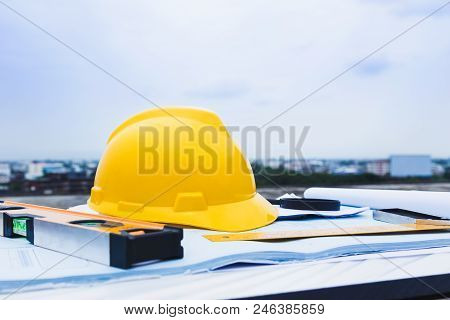 Engineer Constrction Safety Helmet And Other Tools On Top Of Building Blueprint Outside At Construct