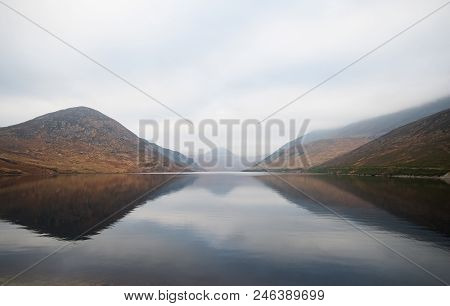 A misty view with reflections of mountains across the Silent Valley Reservoir