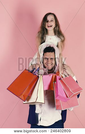 Schoolgirl And Father Do Shopping And Have Fun. Shopping, Presents And Family Concept. Daughter Sits