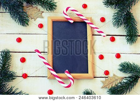Christmas, New Year Background, Candy, Spruce Branches, Golden Leaves, Blackboard On White Wooden Ta