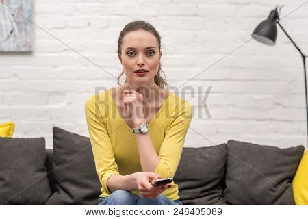 Beautiful Adult Woman With Remote Control Watching Tv While Sitting On Couch