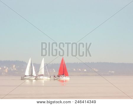 Three Sailboats In The Distance On The Horizon In A Quiet, Windless Weather. Two White Sailboats And