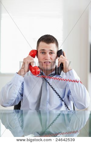 Stressed businessman getting overextended by the telephone