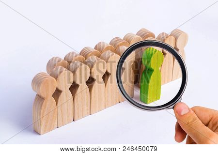 The chosen person among others. A human figure of green color stands out from the crowd. Wooden figures of people. A talented worker, a successful choice. Promotion. Concept of search for a worker.