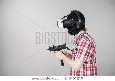 Man Playing Video Game Wearing Virtual Reality Device Holding Gun. Gaming Equipment For Gamers Conce