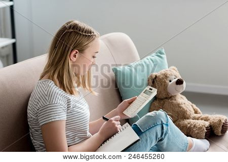 Teen Student Girl Writing In Notebook And Using Calculator While Sitting On Couch