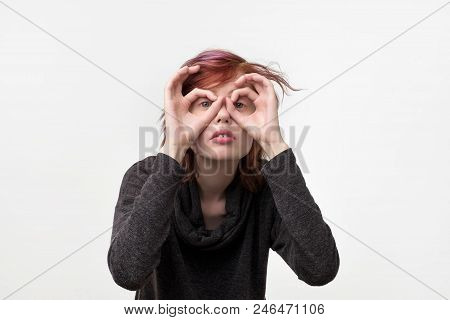 Portrait of unusual informal pretty woman with colorful hairstyle gazing through imaginary glasses made from fingers. Trying to see small details or someone secret poster