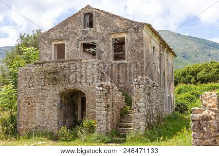 Ancient House Built With Concrete. Flowering Plants Growing In The Ground. Wooden Blocks Falling Fro
