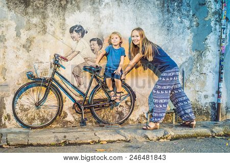 Georgetown, Penang, Malaysia - April 20, 2018: Mother And Son On A Bicycle. Public Street Art Name C